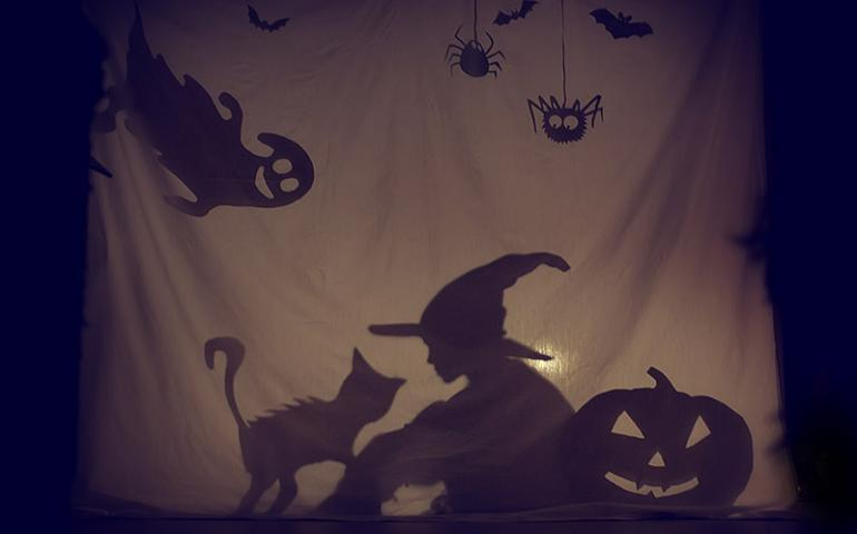Shadow of kid with witch hat and other halloween paraphernalia
